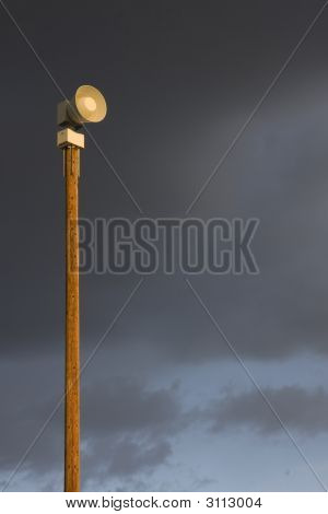 Warning Siren On A Tall Post Against Stormy Sky