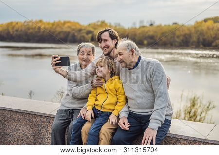 Senior Couple With With Grandson And Great-grandson Take A Selfie In The Autumn Park. Great-grandmot