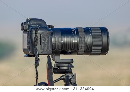Camera With Tripod Close Up In Desert.