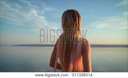 Girl In A Light Dress On The Beach At Sunrise. Beautiful Women In A Light Pink Dress Walking Along T