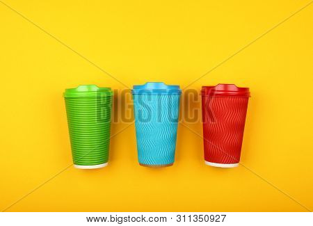 Close up three crimped disposable paper takeaway coffee cups, red, green and blue, with plastic cap over vivid yellow background, flat lay, elevated top view, directly above poster