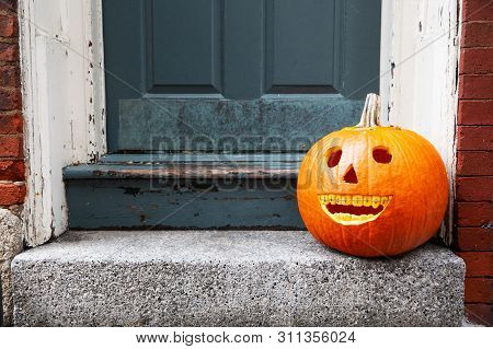 Funny Halloween Pumpkin On The Doorstep. Smiling Pumpkin With Braces. The Concept Of Dentist Office.