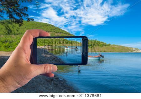 Hand Taking Picture With A Smartphone On The Coast In Sunny Day Of Summer
