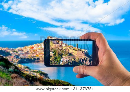 Hand Taking Picture With A Smartphone Of The Village Of Castelsardo, In Sardinia