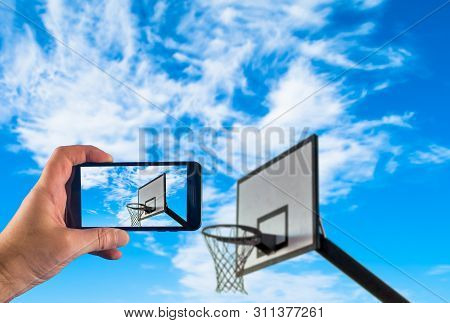 Hand Taking Picture With A Smartphone Of Basketball Hoop With Cloudy Blue Sky