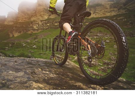 Rear View Wide Angle Partly A Man On A Mountain Bike Travels On Rocky Terrain. The Concept Of A Moun