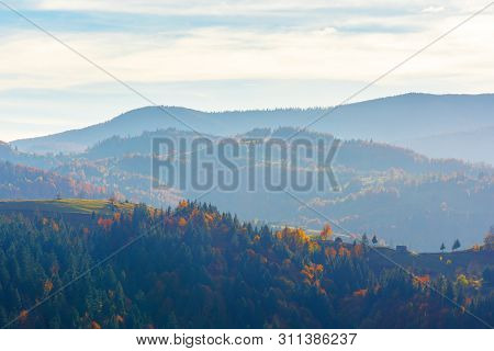 Beautiful Autumn Afternoon In Mountains. Hazy Atmosphere And Clouds On The Sky. Trees In Fall Foliag