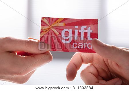 Close-up Of Female Hand Giving Gift Card To Her Male Partner