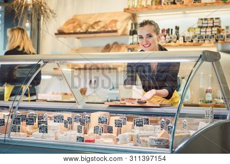 Young Sales lady at the cheese counter in a supermarket working