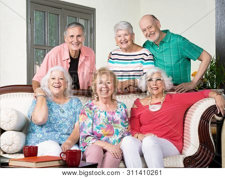 Six Happy Senior Friends Around An Antique Couch