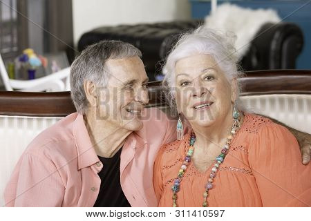 Senior Man And Lady At Home On A Couch