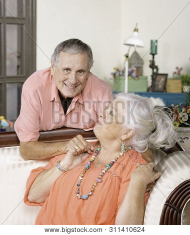 Senior Man And Woman At Home On Couch Laughing