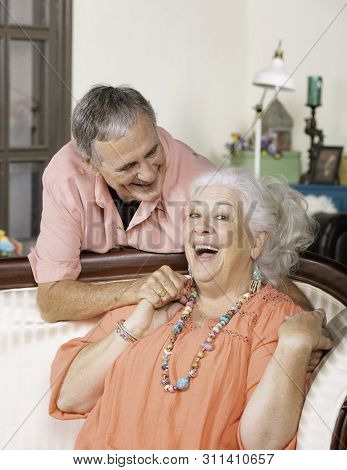 Affectionate Senior Man And Woman At Home On Couch Smiling