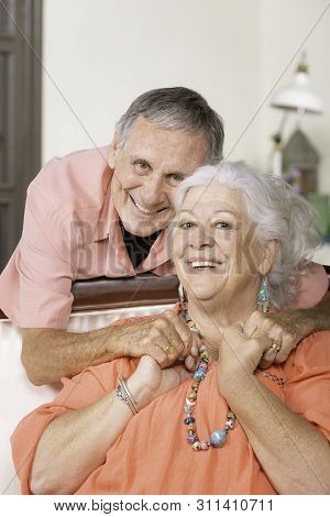 Cheerful Senior Man And Woman At Home Holding Hands