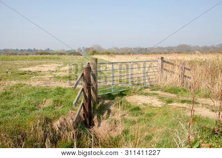 Farmland Gate. Country Walk Along Rural Norfolk Broads Farm Land Path Uk. Wood And Metal Gate In The