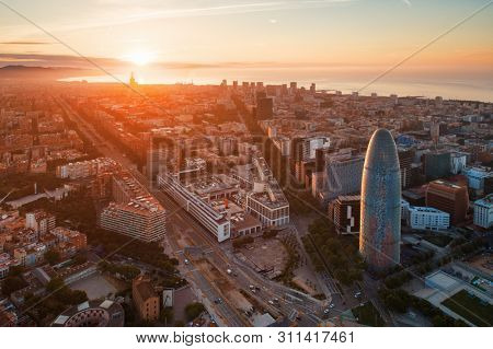 BARCELONA, SPAIN – MAY 13, 2019: Aerial view of city buildings and The Torre Glories in business district at sunrise.