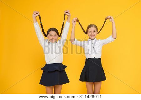 Long hair growth stimulant. Cute small children holding long hair braids on yellow background. Adorable little girl being proud of long hair. Wearing long hair in plaits for school. poster