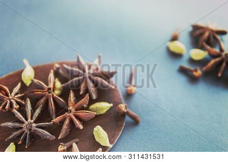 Dry Star Anise Clove And Cardamom On A Brown Wooden Spatula. Natural Food Spices And Seasonings. Tas