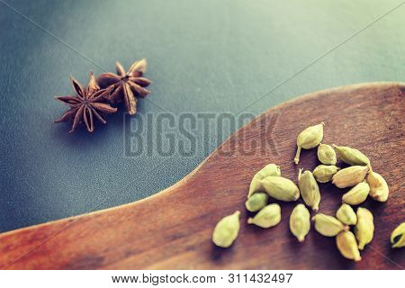 Dry Star Anise And Cardamom On A Brown Wooden Spatula. Natural Food Spices And Seasonings. Tasty Eat