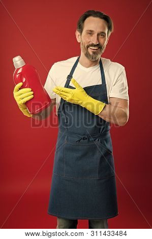 Cleaning day today. Bearded guy cleaning home. Cleanliness and order. Cleaning service and household duty. So dirty. Man in apron with gloves hold plastic bottle liquid soap chemical cleaning agent. poster