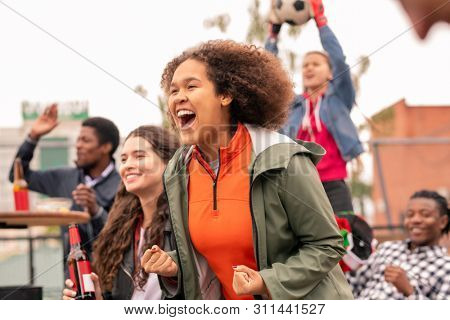 Ecstatic intercultural friends cheering for their football team after goal