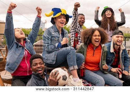 Young intercultural football fans with raised hands cheering for their team