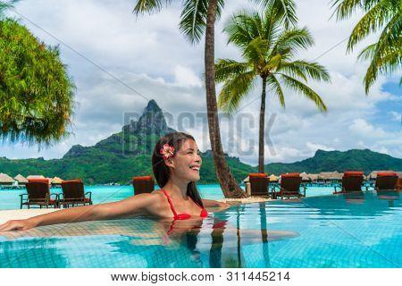 Luxury hotel vacation resort Asian woman tourist relaxing in swimming pool enjoying tropical getaway in Bora Bora, Tahiti, French Polynesia.
