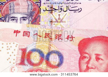 A multicolored one rial note from Oman, close up in macro with a red, Chinese one hundred yuan renminbi bill poster