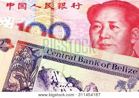 A colorful two dollar bill from Belize in close up macro with a red, Chinese one hundred yuan renminbi note poster