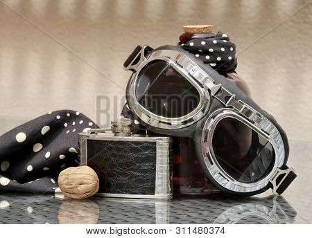 Still Life With Aviation Style Goggles, Black Vintage Hip Flask, Polka Dot Headscarf And Walnut. Sha