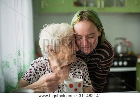 Portrait of elderly woman with her granddaughter at the table in the kitchen at home.