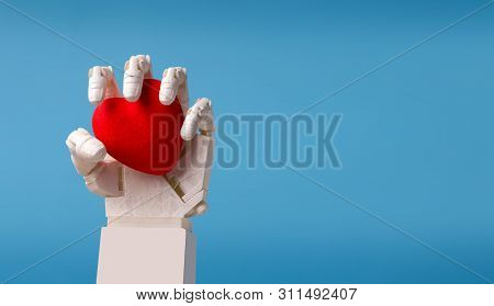Loving The Future Concept. Robot Hand Holding Red Heart, Blue Panorama Background With Empty Space