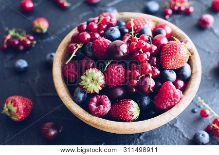 Bowl Of Various Summer Organic Berries. Large Collection Of Freshly Picked Ripe Berries On Black Bac