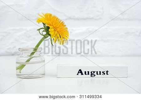 Wood Calendar Summer Month August And Yellow Dandelion In Bottle Vase On Table Background White Bric