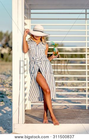 Sexy Woman Is Wearing Long Linen Stripped Dress And Hat With Tanned Skin And Perfect Figure Is Stand