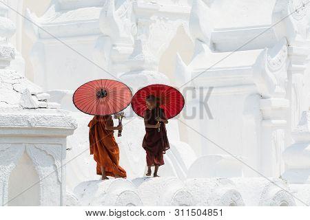 Mandalay, Myanmar - April 2019: Buddhist Novice Monks With Red Umbrellas Walking On The Walls Of Mya