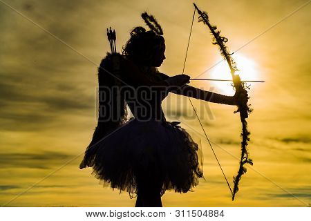 Teen Angel Girl Archer On Sunset. Silhouette Of A Cupid. Cute Teen Cupid On The Cloud - Sky Backgrou