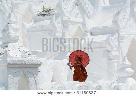 Mandalay, Myanmar - April 2019: Buddhist Novice Monk With Red Umbrella Walking On The Walls Of Myath
