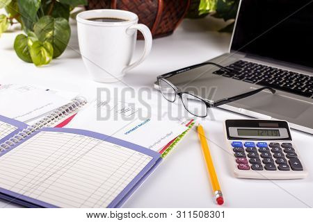 Home Finance Planner And Bill Organizer With Office Accessories On A White Desktop