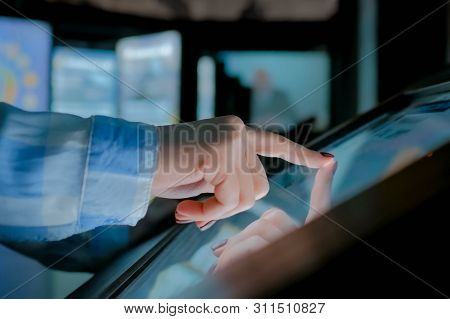Woman Using Interactive Touchscreen Display Of Electronic Multimedia Kiosk At Modern History Museum.