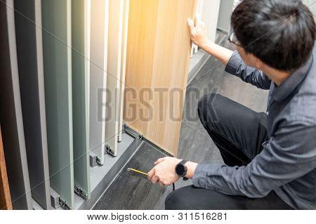 Asian Man Choosing Cabinet Panel Materials Or Countertops For Built-in Furniture Design. Shopping Fu