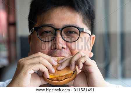 Asia Man Is Eating Hamburger In A Fast Food Restaurant And Enjoying Delicious Food. Man In A White T