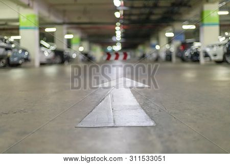 Underground Parking At Supermarket With White Arrow Sign For Exit Way. Abstract Blur Image Carpark B