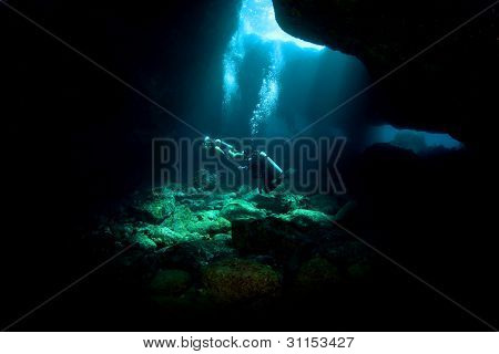 Divers Exploring A Lava Tube