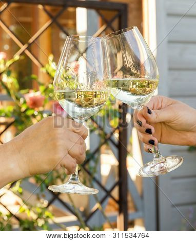 Family Of Different Ages People Cheerfully Celebrate Outdoors With Glasses Of White Wine, Proclaim T