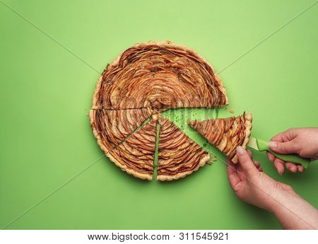Woman Taking A Slice Of Rose Flower-shaped Apple Pie On A Knife, On A Green Paper Background. Flat L