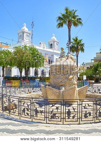 Barbate, Spain - June 25, 2019. Monument statue to the Fisherman with the Barbate Town Hall in the background. Plaza De La Inmaculada Square. Barbate, Andalusia, Spain.
