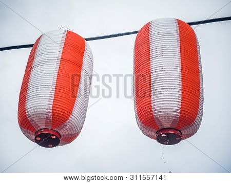 Two Paper Red-white Japanese Lanterns Chochin Hanging On Garland Sky Background