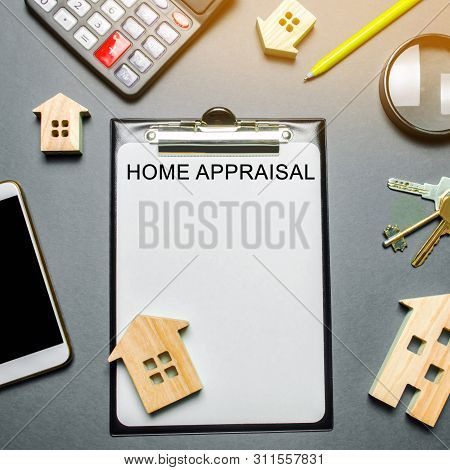Table With Wooden Houses, Calculator, Coins, Magnifying Glass With The Word Home Appraisal. The Cont
