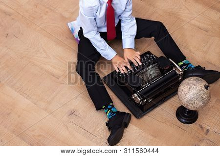 The Boy Is Typing On An Old Typewriter. Schoolboy With A Vintage Machine. The Boy Sits On The Floor